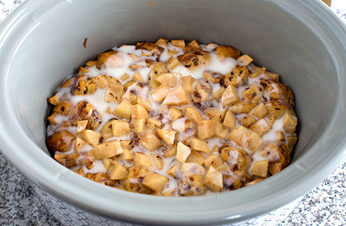 cookedCrock Pot Apple Cinnamon Roll Casserole with icing in a grey slow cooker