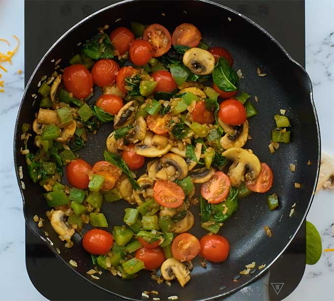 vegetables being sautéed in a skillet