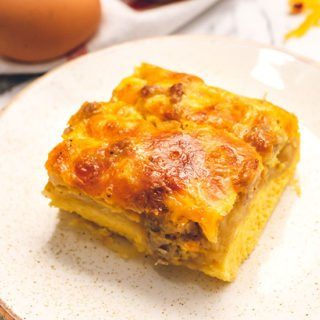 piece of breakfast casserole with sausage, eggs, cheese, and crescents