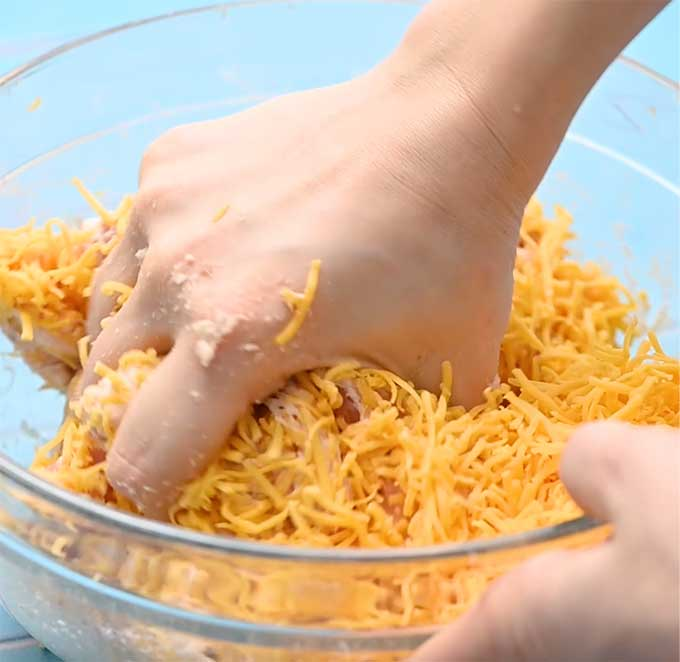Bowl of sausage, Bisquick, and shredded cheese being hand mixed.