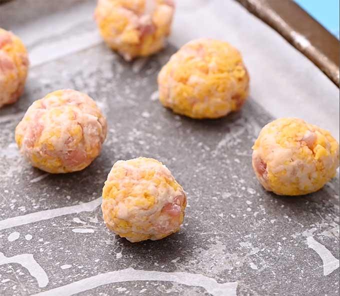 Uncooked sausage balls on a baking sheet